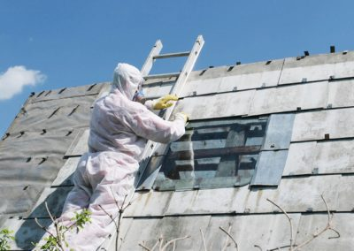 Photo of worker in hazmat suit working on pitched roof