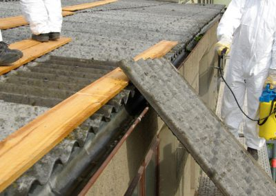 photo of men working on roof, removing asbestos panels